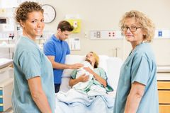 Successful Nurses Standing Against Couple With Stock Photos