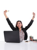 Successful office lady expressing her joy. Successful Asian female office worker raising both arms in happiness while looking at her laptop screen, isolated on Royalty Free Stock Photo
