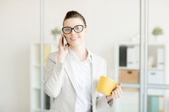 Young office manager. Successful office manager with yellow mug speaking by smartphone before coffee break royalty free stock photos