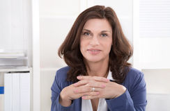 Successful older business woman sitting at office. Royalty Free Stock Photography