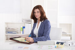 Successful older business woman sitting at office. Stock Photos
