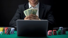 Successful online casino player counting money in front of laptop, bet winner. Stock photo stock photos