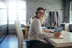 Successful online store owner. Happy woman business owner writing notes in diary. Online store working at her desk stock image