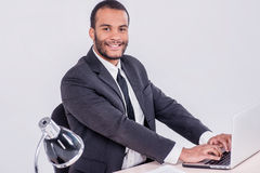 The successful operation. Smiling African businessman sitting at Stock Photo