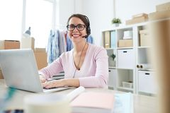 Successful operator looking at you while consulting online clients. In front of laptop in office royalty free stock photo