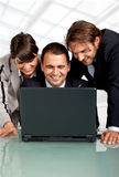 Successful partners. Three happy businesspeople with a laptop, laughing royalty free stock photo