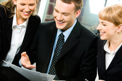 Successful partners. Photo of a young successful businessman between two business ladies looking at document in his hands with happy smiles stock image
