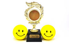 Successful partnership. A photo of two smiley faces on either side of a trophy, describing a successful partnership, team or friendship. A photo can be placed on royalty free stock photography