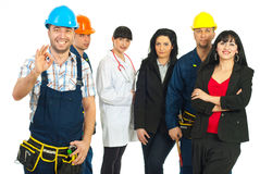 Successful people with different careers. Happy constructor worker showing okay sign hand gesture in front of people group with different careers over white Stock Photos