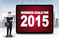 Successful person with business goals for 2015. Male entrepreneur with a cardboard head standing in the office next to the board with business goals for 2015 Royalty Free Stock Photo