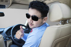 Successful person showing thumb up in car Stock Images