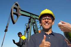 Successful Petroleum Engineers at Oil Well. Successful petroleum engineer showing thumbs up and celebrating opening of a new oil source with a bottle of stock photo
