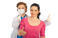 Successful plastic surgery. Successful doctor giving thumbs up together with patient woman prepared for plastic surgery against white background royalty free stock images