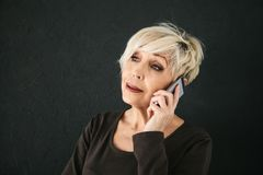 A successful positive elderly female consultant is negotiating a cell phone. Communication between people using modern. Technology. An elderly person at work Stock Photography