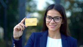 Successful pretty woman look to camera and showing unlimited gold credit card on office building background. Professional female manager wearing glasses and stock video footage