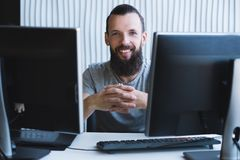 Successful professional career cheerful designer. Successful professional career. Cheerful male web designer sitting at his workplace, smiling royalty free stock photos