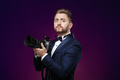 Successful professional photographer in tuxedo use DSLR digital camera on dark background. Young successful professional photographer in tuxedo use DSLR digital Stock Photography