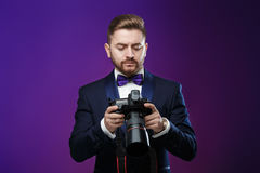Successful professional photographer in tuxedo use DSLR digital camera on dark background Stock Photos