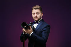 Successful professional photographer in tuxedo use DSLR digital camera on dark background. Young successful professional photographer in tuxedo use DSLR digital Stock Photos