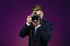 Successful professional photographer in tuxedo use DSLR digital camera on dark background. Young successful professional photographer in tuxedo use DSLR digital Royalty Free Stock Image