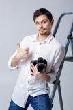 Successful professional photographer use DSLR digital camera on. Young successful professional photographer in shirt use DSLR digital camera on grey background Royalty Free Stock Photo