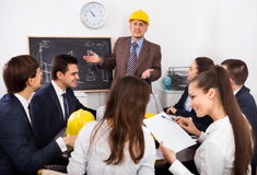 Successful professionals with laptops and helmets Royalty Free Stock Photos