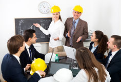 Successful professionals with laptops and helmets Stock Image
