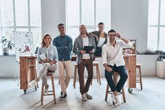 Successful professionals. Full length of young modern people in smart casual wear smiling and looking at camera while standing in the creative office royalty free stock image