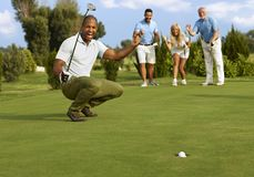 Successful putt. Male golfer and partners happy for successful putt on the green royalty free stock images