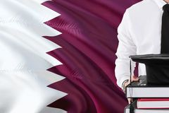 Successful Qatari student education concept. Holding books and graduation cap over Qatar flag background.  stock images