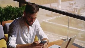 Caucasian realtor working with laptop and chatting with client on smartphone. Successful realtor working with laptop at cafe table and typing message to client stock footage