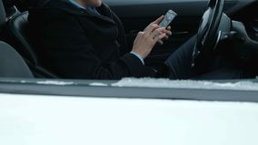A successful respectable businessman at the wheel of an expensive car uses the phone. 4k stock video