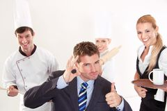 Successful restaurant staff. Restaurant menager with his staff gesturing thimb up sign Stock Photography