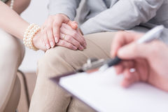 Successful results of a professional marital therapy. Close-up of married couple's hands in an affectionate pose and a blurred flipboard with somebody writing on Stock Photos