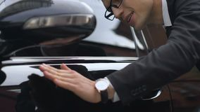 Successful rich businessman admiring newly purchased auto, car loan or purchase. Stock footage stock video