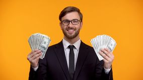 Successful rich man showing bunch of dollars in hands, easy income on internet. Stock photo royalty free stock photography