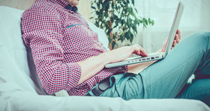 Successful Risk Manager working Laptop modern Interior Design Loft Office.Men work Vintage Sofa,Using contemporary. Smartphone Hand Calling.Blurred Background Stock Photos