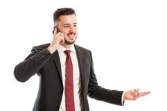 Successful sales man. Concept with a suited male talking on the phone and smiling on white background stock photography