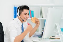 Successful sales manager. Young manager with a burger in his hand being happy about successful sales Stock Images