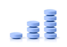 Successful sales on pharmacy market. Growth graph made of blue pills stacked in columns - increasing on-line market, demand and usage of blue pill and it's Royalty Free Stock Images