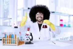 Successful scientist with ok sign and chemical liquid. Successful scientist smiling at camera while showing thumbs up and chemical liquid in the laboratory Royalty Free Stock Photography