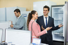 Successful  seller and happy  couple at household appliances sec Royalty Free Stock Photos