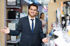 Successful  seller and happy couple at household appliances sect Stock Image