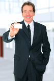 Successful Senior Businessman. Happy senior caucasian businessman holding up empty blank business card on his hand Stock Photos