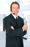 Successful Senior Customer Representative Smiling. Senior customer service talking on the headset and give an ok sign Stock Image