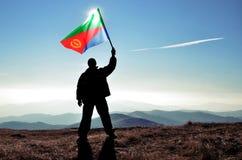 Successful silhouette man winner waving Eritrea flag Stock Photos