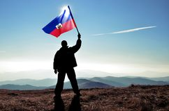 Successful silhouette man winner waving Haiti flag on top of the mountain. Peak stock photo