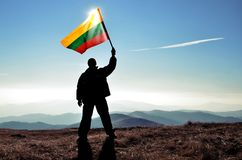 Successful silhouette man winner waving Lithuania flag Royalty Free Stock Photo