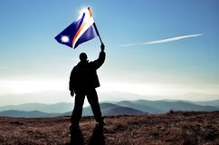 Successful silhouette man winner waving Marshall Islands flag Royalty Free Stock Photography