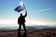 Successful silhouette man winner waving NATO flag on top of the mountain. Peak royalty free stock images